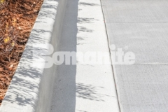 The decorative concrete curbs and walkways created here feature the Bomanite Sandscape Refined Exposed Aggregate System, and the use of a white color hardener in combination with locally sourced aggregates and crushed mirror glass adds the distinctive effect of the sun reflecting off water.