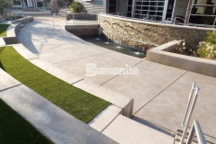 Sandscape Refined Antico decorative concrete by Bomanite was installed here with saw cuts that radiate outward from the baptismal pool to form a courtyard area with seating areas, viewing sections, and various gathering spaces.