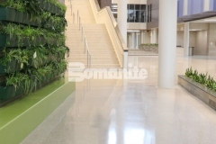 The Bomanite Renaissance Deep Grind process involves treating the floor with chemical hardeners that reduce porosity while still allowing it to breath, providing superior stain resistance and natural wear for a custom polished concrete flooring surface with a high-end aesthetic.