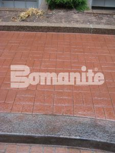 Closeup of curb and Bomanite Basketweave Brick pattern of Bomanite Imprint Systems installeed by Connecticut Bomanite Systems at commercial building pavillion.